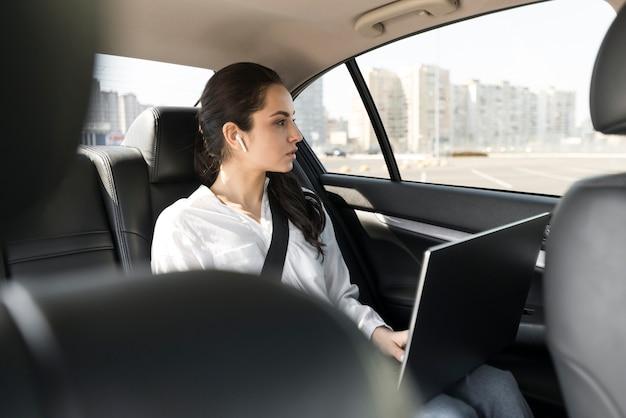 Mulher que trabalha em seu laptop no carro