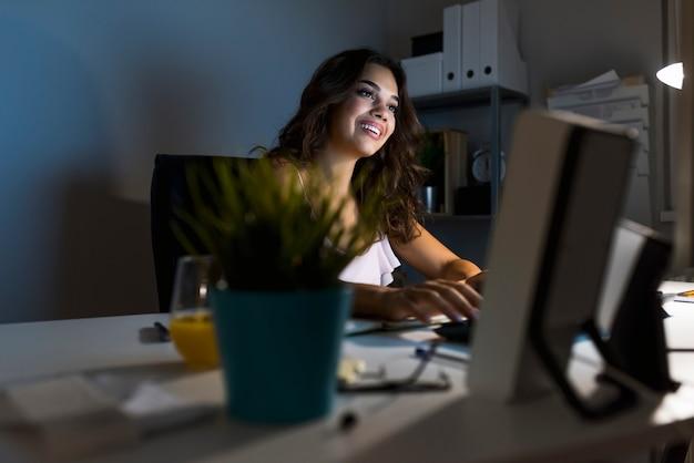 Mulher que trabalha em um computador em casa.