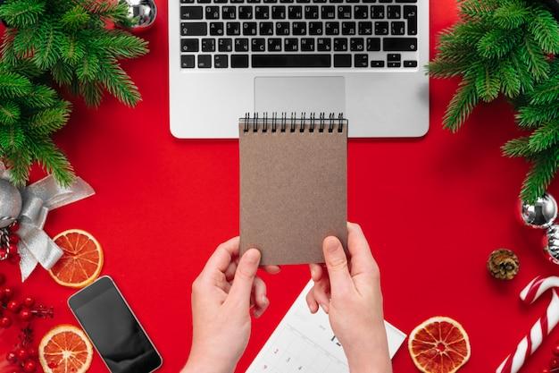 Mulher que trabalha em uma mesa de escritório com decorações festivas de natal