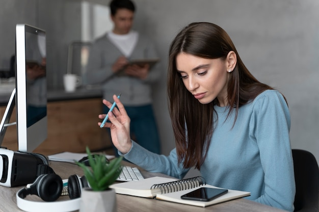 Mulher que trabalha na área de mídia com computador pessoal e smartphone