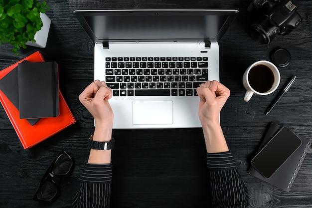 Mulher que trabalha na mesa do escritório. vista superior das mãos humanas, teclado do laptop, uma xícara de café, smartphone, notebook e uma flor sobre um fundo de mesa de madeira.