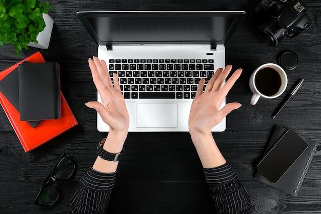 Mulher que trabalha na vista superior da mesa do escritório do teclado do laptop de mãos humanas, uma xícara de café smartphone ...