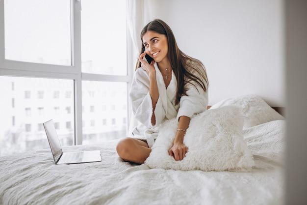 Mulher que trabalha no computador na cama e falando no telefone
