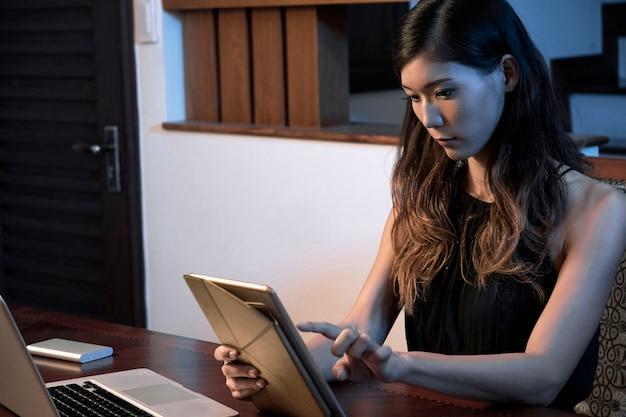 Mulher que trabalha no computador tablet