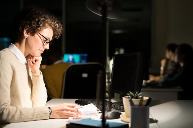 Mulher que trabalha no escritório escuro