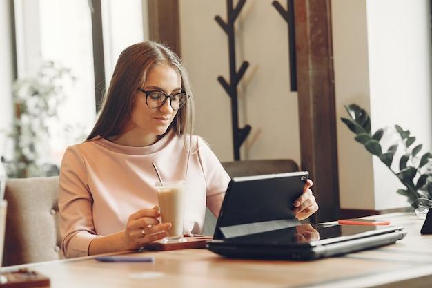 Mulher que trabalha no escritório. senhora com um tablet. mulher em uma blusa branca.