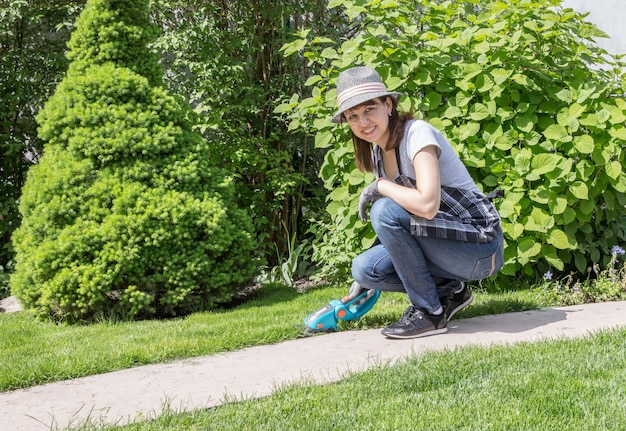 Mulher que trabalha no jardim em um dia ensolarado