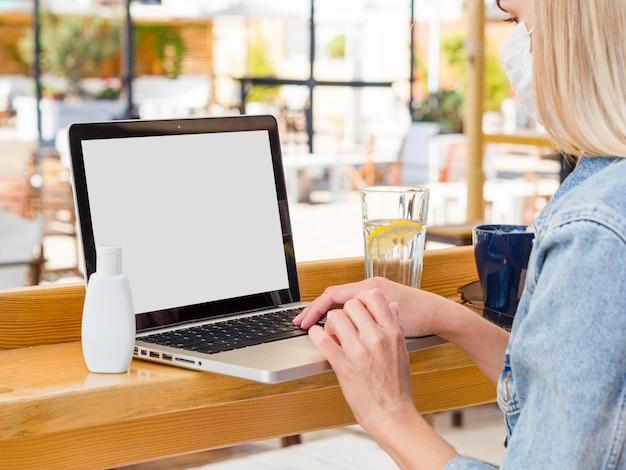 Mulher que trabalha no laptop ao ar livre com desinfetante para as mãos