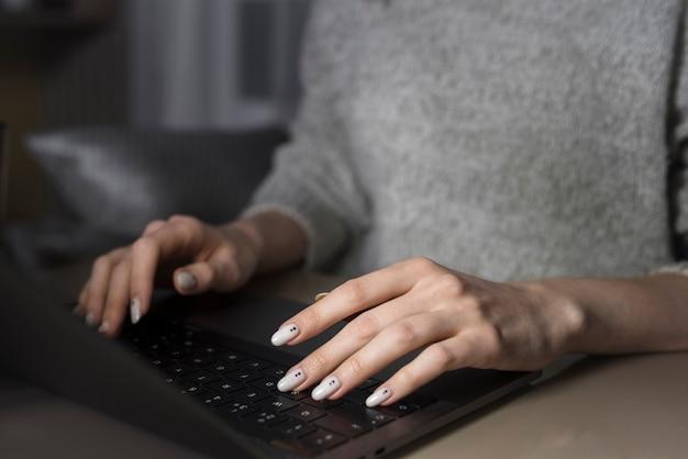 Mulher que trabalha no laptop durante a noite