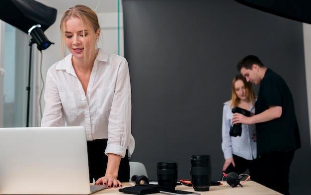 Mulher que trabalha no laptop e pessoas olhando fotos