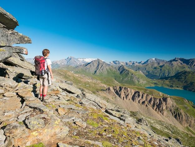 Mulher que trekking na paisagem da montanha rochosa da alta altitude.