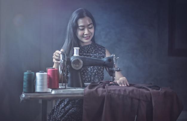 Mulher que usa a máquina de costura vintage. adorável mulher idosa costura roupas