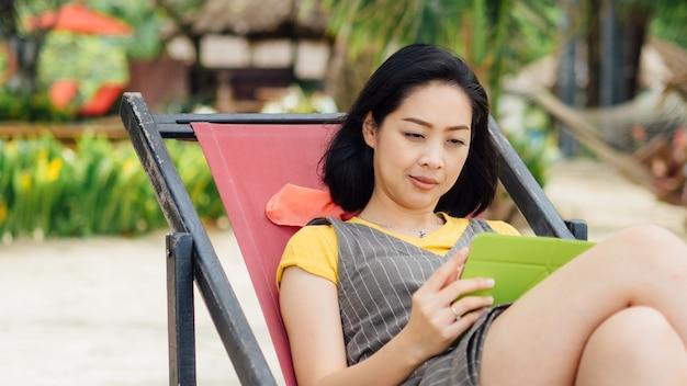 Mulher que usa a tabuleta ao descansar na praia no verão.