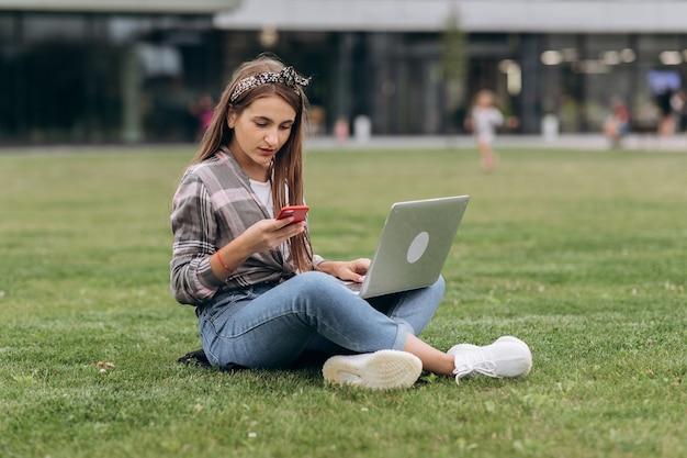 Mulher que usa o computador em gramas verdes no parque. trabalho freelance ao ar livre ou conceito de relaxamento