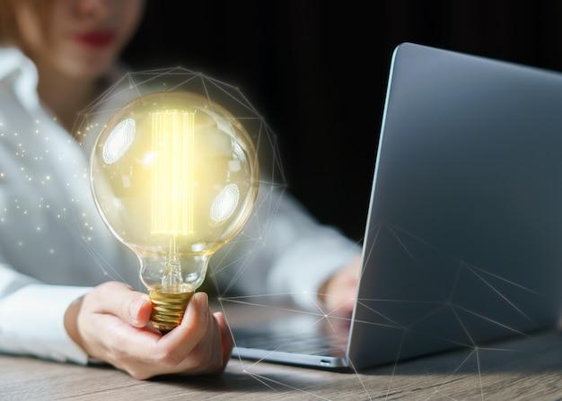 Mulher que usa o computador portátil e mão segurando a lâmpada. conceito de ideia.