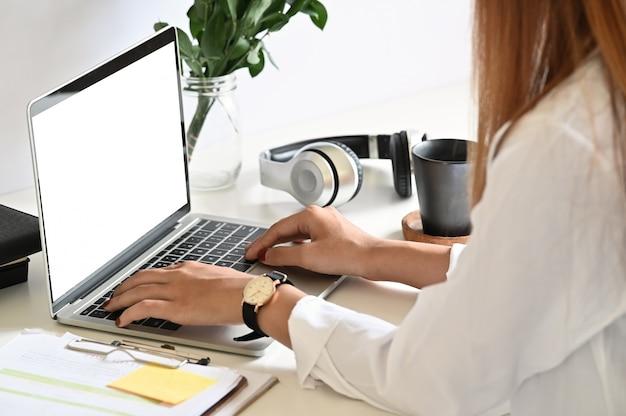 Mulher que usa o portátil do modelo com a tela vazia na mesa de escritório.