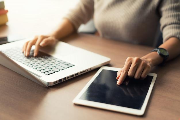 Mulher que usa o portátil e a tabuleta digital durante o trabalho no escritório, mãos perto acima.