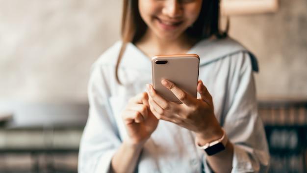Mulher que usa o smartphone, durante o tempo de lazer. o conceito de usar o telefone é essencial na vida cotidiana.