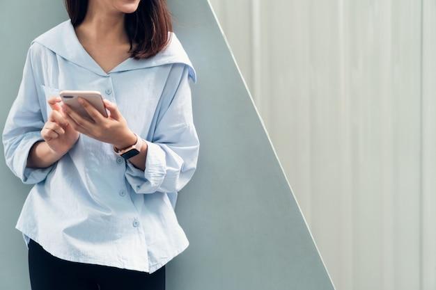 Mulher que usa o smartphone, durante o tempo de lazer. o conceito de usar o telefone é essencial.