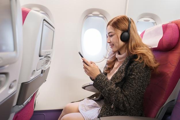 Mulher que usa o smartphone e escutando a música com os fones de ouvido no avião no tempo de voo.