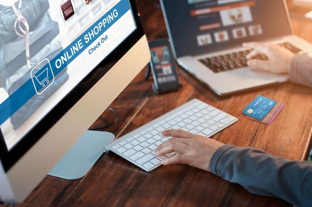 Mulher que usa o smartphone e o portátil do computador para a compra em linha com cartão de crédito em casa.