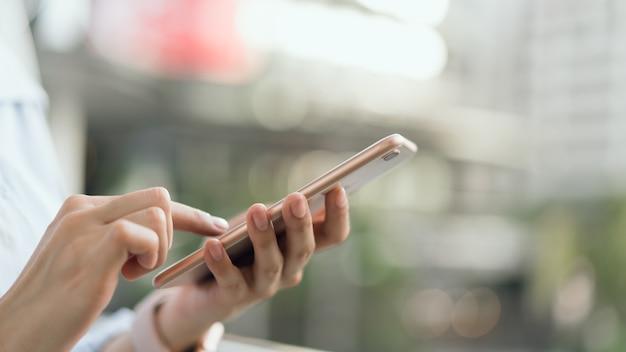 Mulher que usa o smartphone na escadaria em áreas públicas, durante o tempo de lazer.