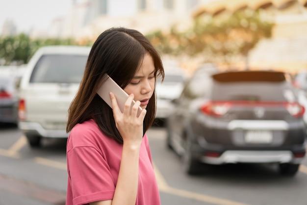 Mulher que usa o smartphone para a aplicação no fundo do borrão do carro.