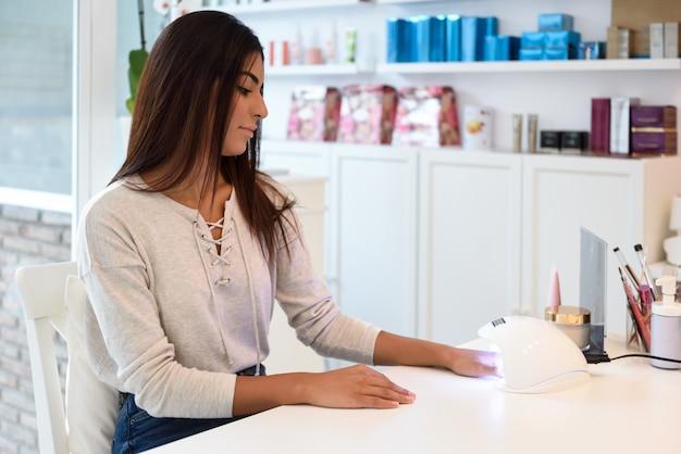 Mulher que usa pregos manicured na lâmpada uv.