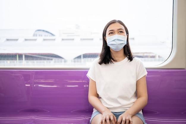 Mulher que usa uma máscara protetora de higiene para proteger os vírus covid19, covid-19 e pm2.5 enquanto viaja em locais lotados.