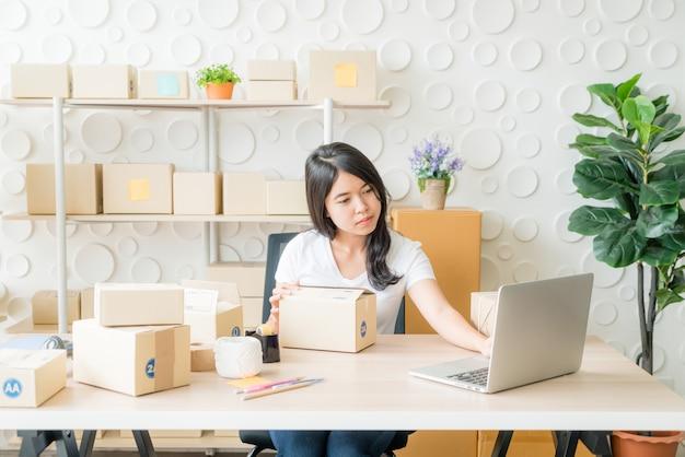 Mulher que verifica a ordem de compra no laptop