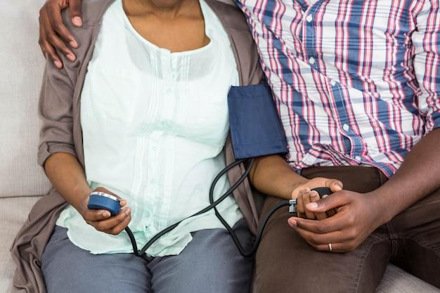Mulher que verifica a pressão sanguínea ao sentar-se com o homem na sala de estar em casa