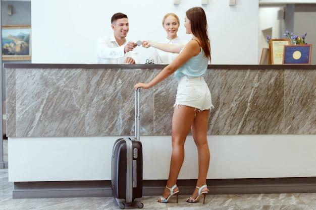 Mulher que verifica dentro na recepção do hotel