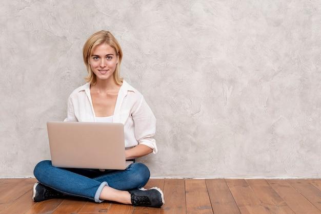 Mulher que verifica o portátil com espaço da cópia