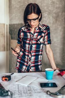 Mulher que verifica planos de projeto para uma cozinha nova