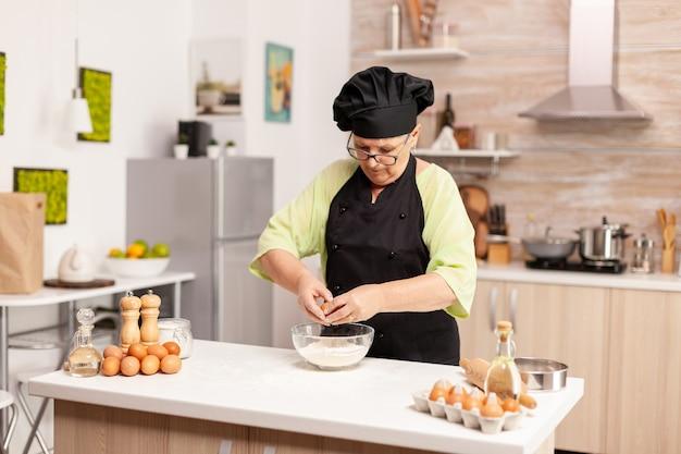 Mulher quebra o ovo acima da farinha, fazendo massa para produtos de panificação. chefe de pastelaria idoso quebrando ovo em uma tigela de vidro para receita de bolo na cozinha, misturando à mão, amassando os ingredientes e preparando o bolo caseiro