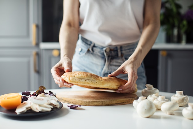 Mulher quebra o pão com as mãos na cozinha iluminada
