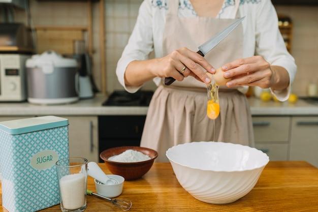 Mulher quebra ovo para fazer torta na cozinha