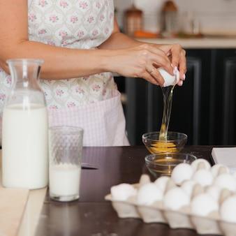 Mulher quebra um ovo branco