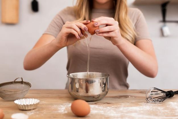 Mulher quebrando ovos em uma tigela metálica