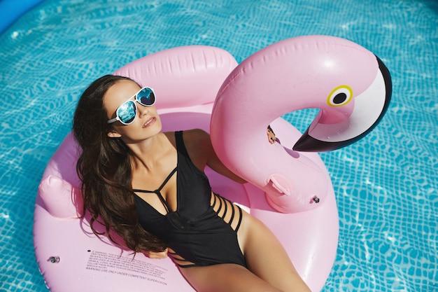 Mulher quente e elegante modelo morena com corpo sexy perfeito em biquíni preto elegante e óculos de sol glamourosos, bronzeando-se em um flamingo rosa flutuante na piscina