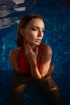 Mulher quente em maiô elegante. retrato de moda ao ar livre da senhora glamour, aproveitando suas férias em uma villa de luxo na ilha tropical quente.
