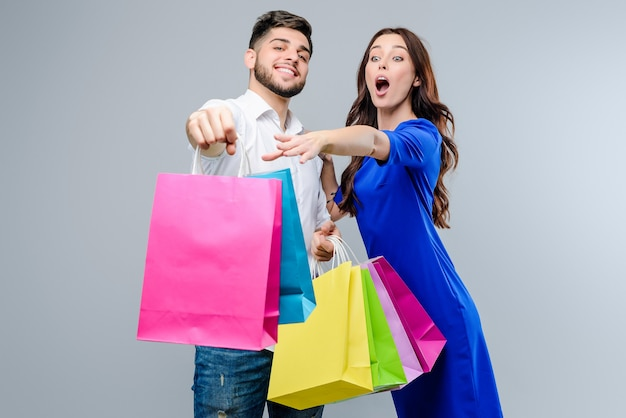 Mulher quer obter sacos de compras do namorado isolado sobre cinza