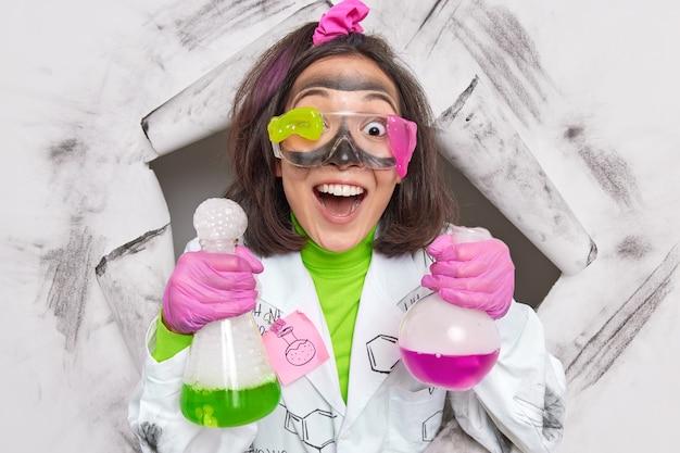 Mulher química realiza trabalho de laboratório para desenvolver e melhorar produtos novos e existentes usa luvas de látex uniformes óculos sujos quebram o papel