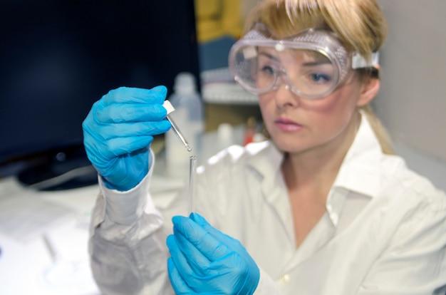 Mulher, químico, em, trabalho laboratório, análise, ligado, médico, amostra, em, tubos teste