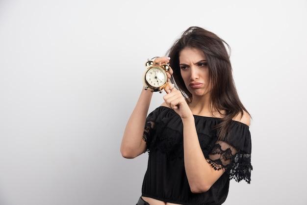 Mulher rabugenta segurando o relógio