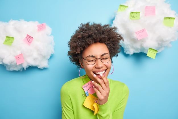 Mulher radiante com cabelos cacheados e sorrindo alegremente usando óculos redondos cercados por notas adesivas isoladas sobre a parede azul