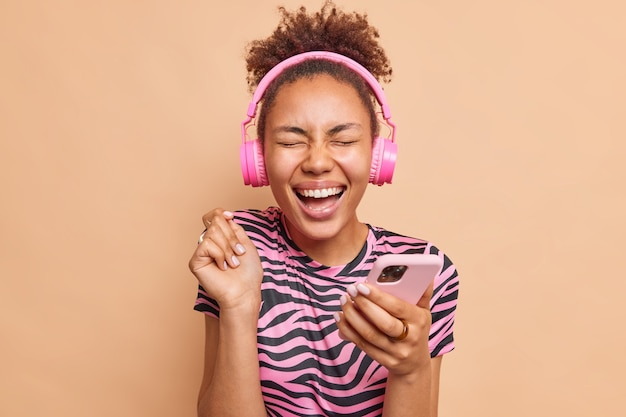 Mulher radiante com cabelos cacheados se regozija excelente notícia mantém o braço levantado usa o telefone celular sorri amplamente mantém os olhos fechados vestido com uma camiseta listrada isolada na parede bege