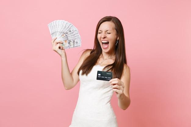 Mulher radiante em um vestido de renda branca gritando, segurando um monte de dólares em dinheiro em cartão de crédito