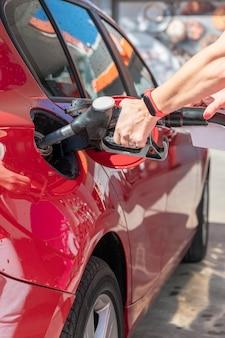 Mulher reabastecendo o carro em um posto de gasolina