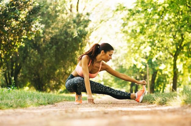Mulher realiza alongamento antes de correr